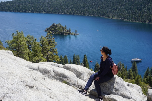 girl sitting on a rock looking at the lake