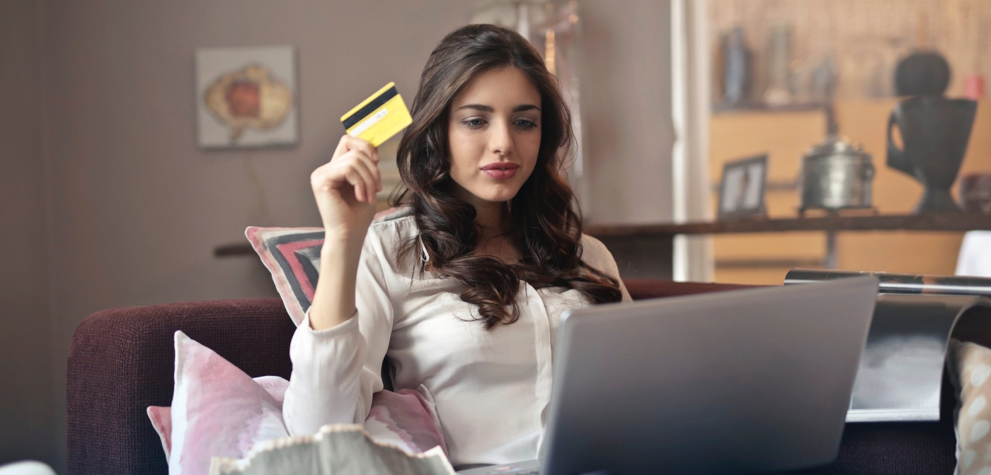 girl holding credit card and looking at laptop