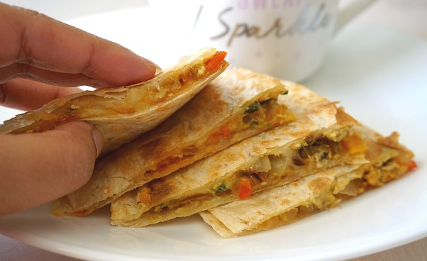 Hand holding Stacked Masala Scrambled Egg Quesadillas on a plate