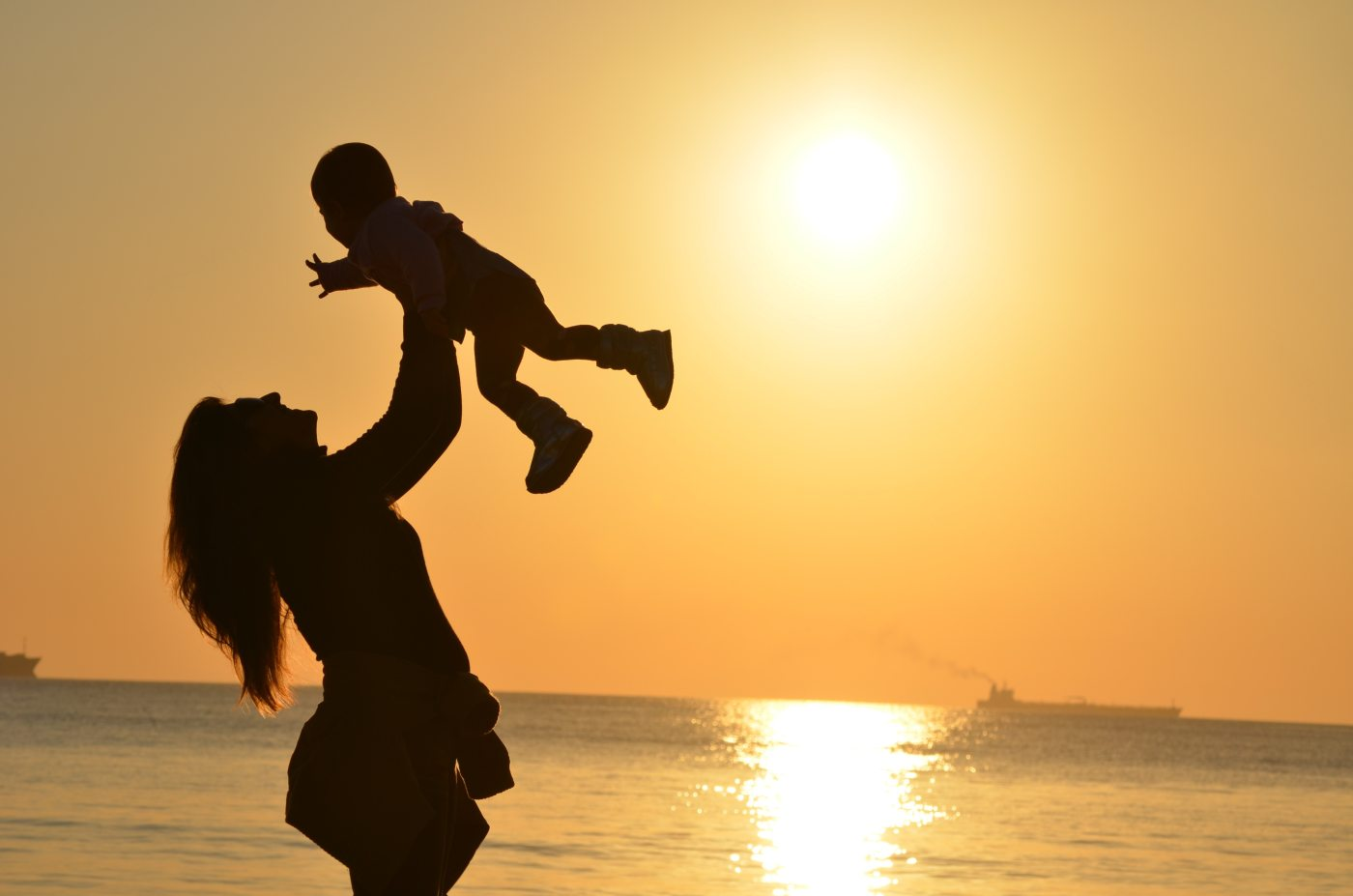 mom holding kid high up in the air
