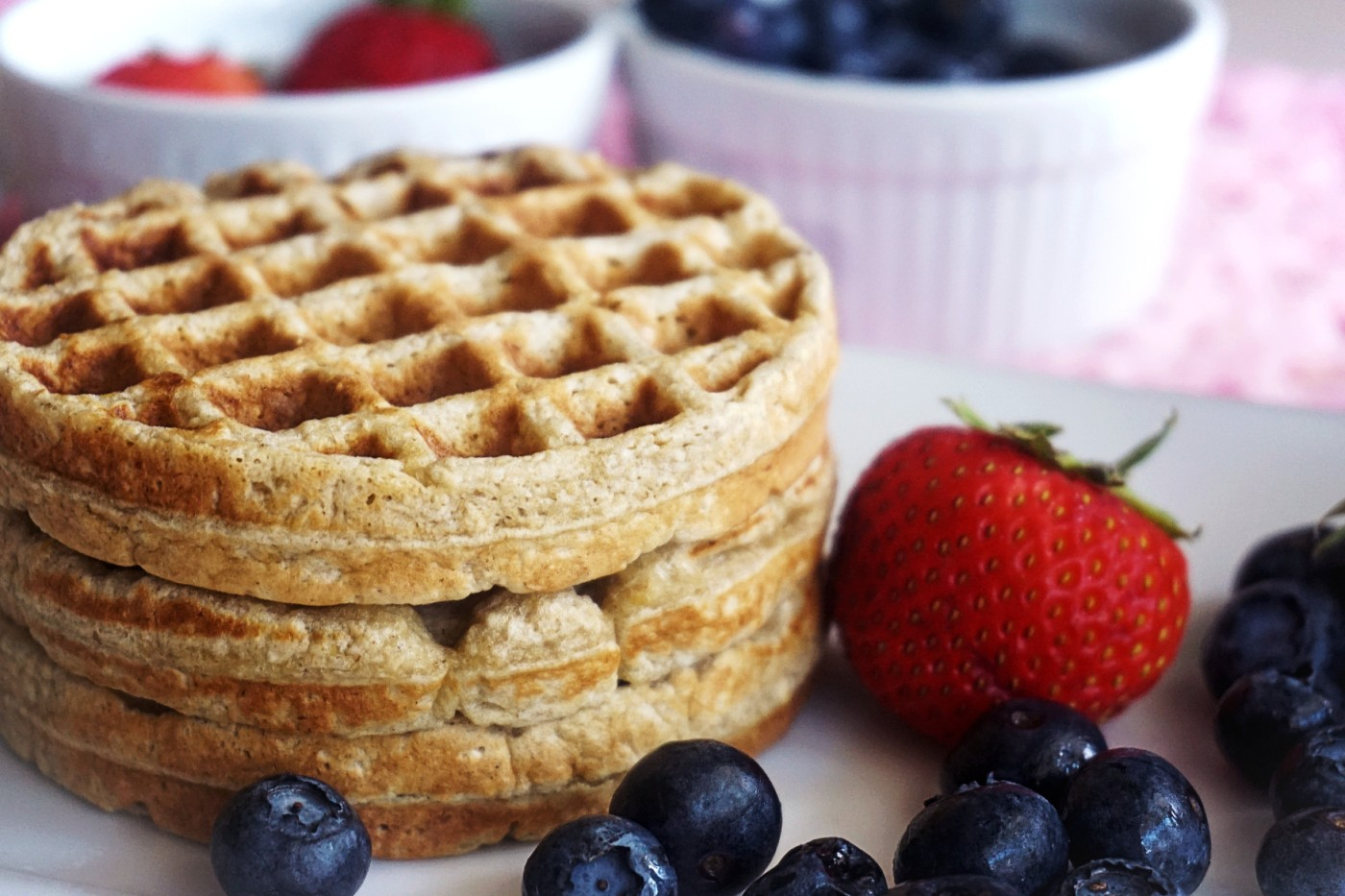 Stack of waffles with fruits by the side